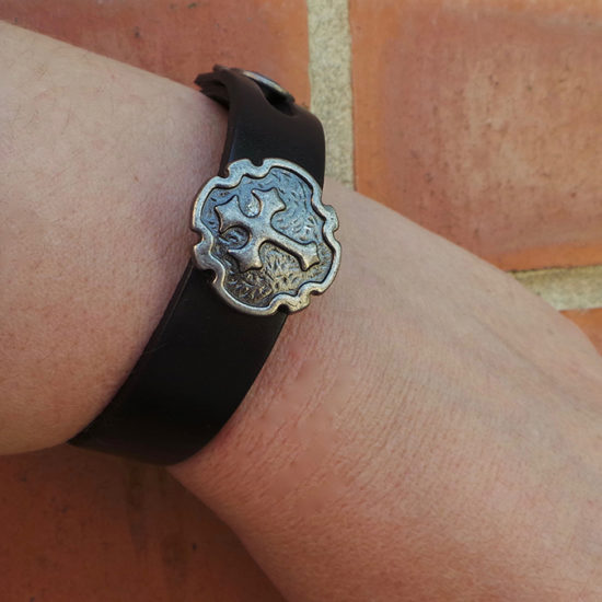 Leather bracelet with cross emblem