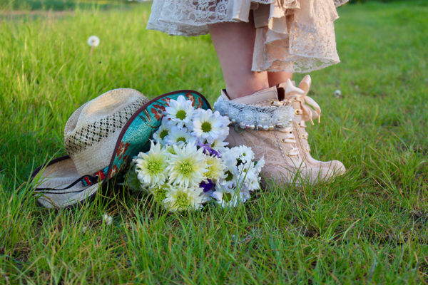 Beautiful boots and hat and flowers in field